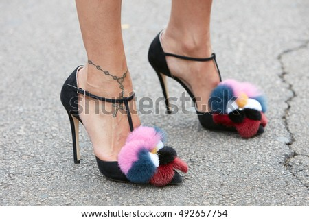 MILAN - SEPTEMBER 22: Woman with high heel shoes with fur details before Fendi fashion show, Milan Fashion Week street style on September 22, 2016 in Milan.