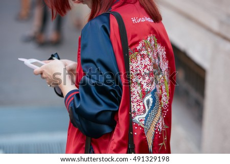 MILAN - SEPTEMBER 22: Woman with red and blue satin bomber jacket before Prada fashion show, Milan Fashion Week street style on September 22, 2016 in Milan.