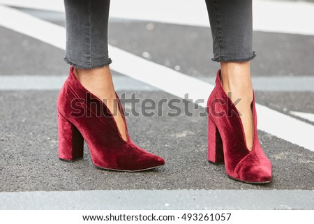 MILAN - SEPTEMBER 23: Woman with red velvet high heel shoes before Giorgio Armani fashion show, Milan Fashion Week street style on September 23, 2016 in Milan.