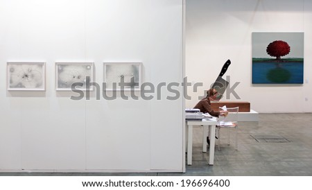 MILANO, ITALY - APRIL 08, 2011: A woman on a chair at paintings galleries during MiArt, international exhibition of modern and contemporary art in Milano, Italy - stock photo