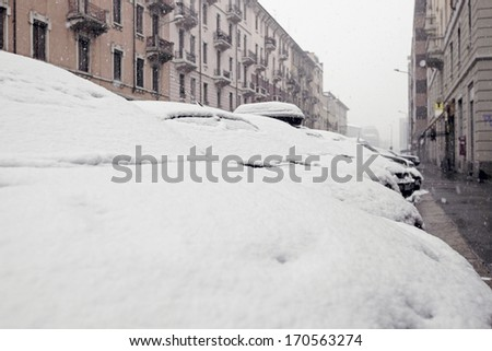 MILANO, ITALY - FEBRUARY 11, 2013: Cars under snow on the street, snow storm in Milano, Italy.
