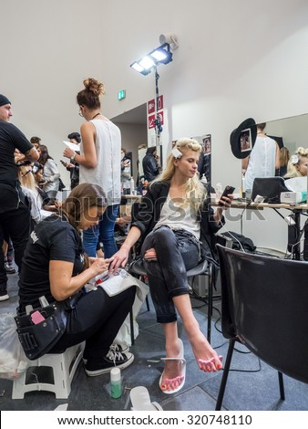MILANO, SEPTEMBER 23, 2015: Staff working on the nails of a model at the backstage of Stella Jean during the presentation of spring-summer 15/16 collection at Milan Fashion Week 2015. - stock photo