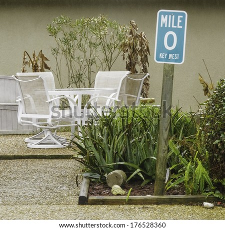 Mileage sign to indicate laid-back lifestyle in yard with tropical plants and patio furniture on a rainy day in Florida - stock photo