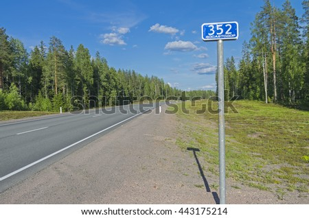 Milepost on the federal highway A121. Sunny day in June. South Karelia, Russia.