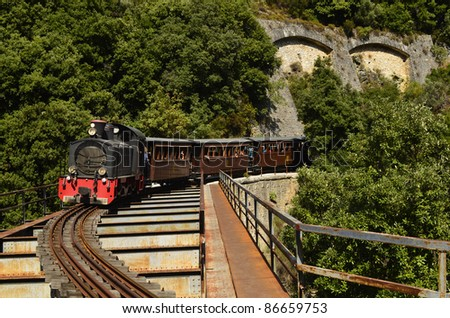 MILIES, GREECE - SEPTEMBER 25: the weekly nostalgic tourist Montzouris-Smudgy train - also named Pelion train - crossing a bridge in the mountains of Pelion on September 25, 2011 in Milies, Greece - stock photo