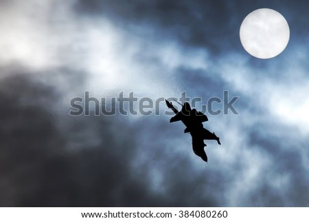 Military aircraft performing aerobatics in the cloudy sky and the sun a the background - stock photo