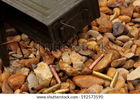 Military ammunition box and spent cartridge casings on a wet gravel beach - stock photo