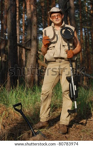 Military archeology. Man with metal detector and German WWII time horse-shoe. Eastern Europe - stock photo