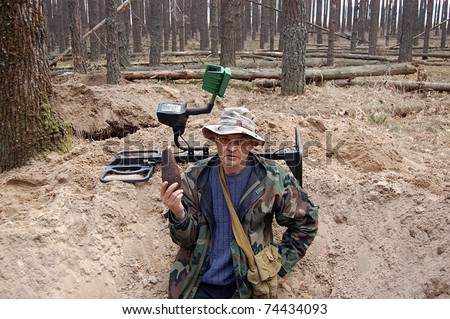 Military archeology. Man with metal detector and Soviet 82-mm mortar shell remains on the battlefield of WW2. - stock photo