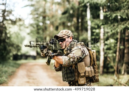 military. Armed young man in a zone of armed conflict soldier in uniform targeting with assault rifle outdoors, airsoft