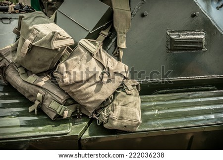 Military canvas kit bags hanging over an armoured car. - stock photo