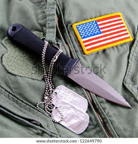 Military dog tags, boot knife and American Flag patch on pilot flight suit - stock photo