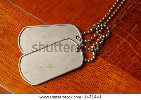 military dog tags on a teak wooden table