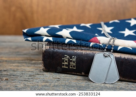 military dog tags on American flag and worn Holy Bible - stock photo