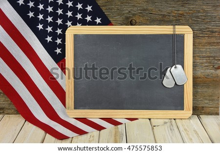 military dog tags on black chalkboard with American flag
