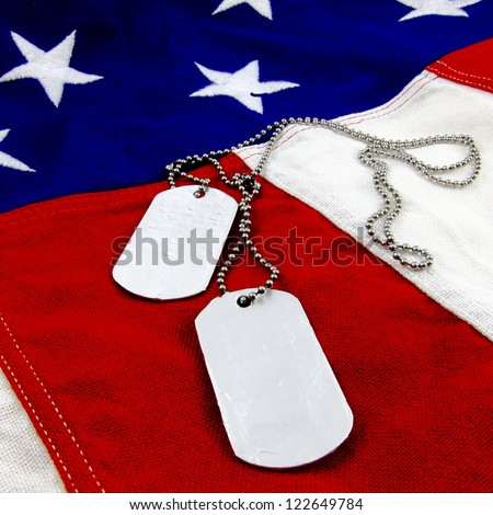 Military dog tags on vivid stars and stripes background - stock photo
