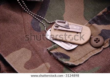 Military Dog Tags resting on camouflage material - stock photo