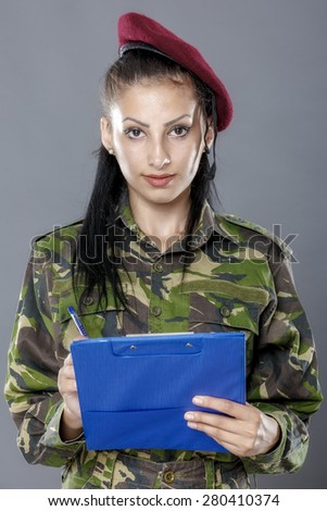 Military female writing in notebook  isolated on gray background - stock photo