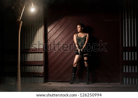 Military girl with a gun in a desserted area - stock photo