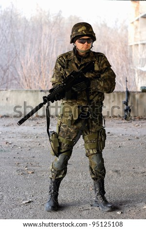 Military guy holding a gun in front of neglected building
