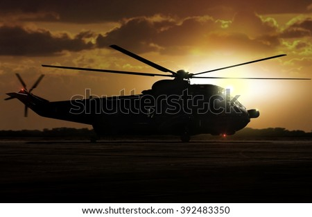 Military helicopter on airfield during sunset - stock photo