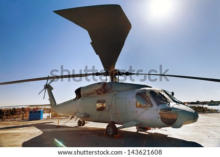 Military helicopter on the carrier deck on sunny day - stock photo