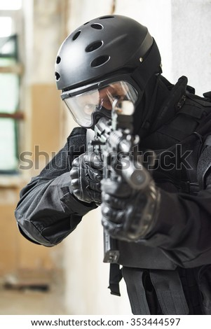 Military industry. Special forces or anti-terrorist police soldier, private military contractor armed with with machine gun ready to attack during clean-up operation