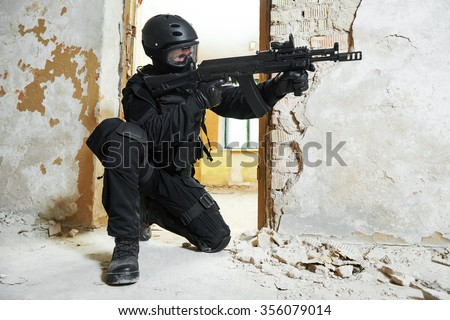 Military industry. Special forces or anti-terrorist police soldier,  private military contractor armed with assault rifle ready to attack during clean-up operation, mission - stock photo