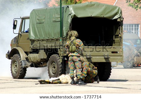military intervention.  soldier in action. War concept. War victim, injured soldier being rescued. - stock photo