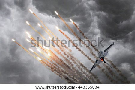 Military jet firing of flares, stormy sky - stock photo