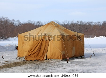 Military khaki tent in the snow polar region in a forest. - stock photo