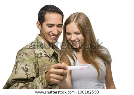 Military Man and His Wife Smile at Pregnancy Test - stock photo