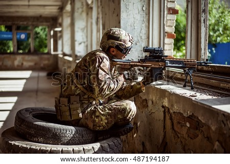 Military man sniper with automatic rifle with a telescopic sight sitting by the window in building