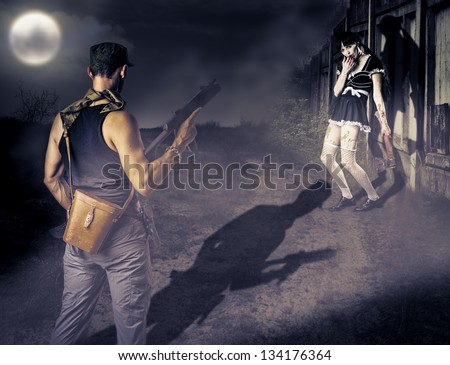 Military man with a gun looking at female zombie with a bloody ax - stock photo