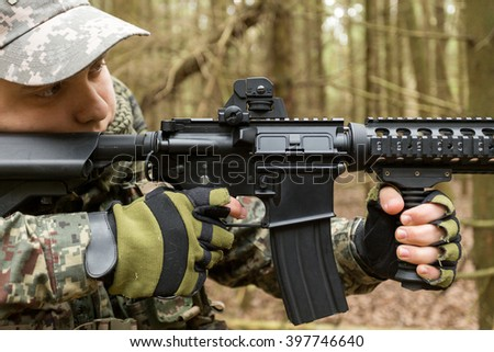 Military man with Rifle M16 outdoor forest, close-up, hands holding automatic weapons - stock photo