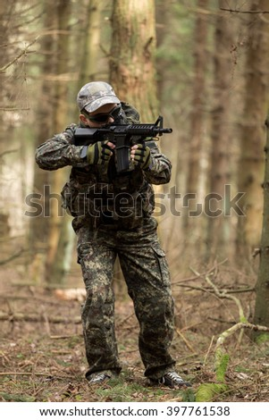 Military man with Rifle M16 outdoor forest, full-length