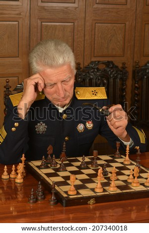 Military mature general on the table playing chess - stock photo