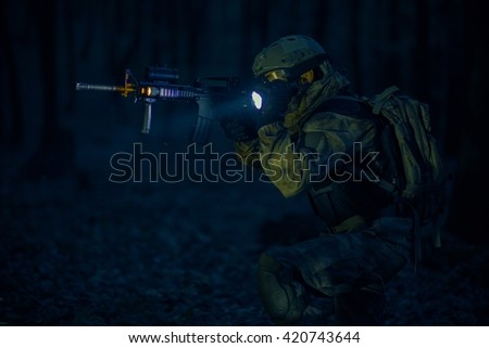Military Night Operation. Soldier with Assault Rifle and Flashlights at Night. - stock photo