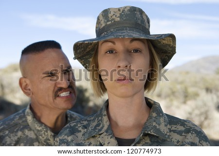 Military officer screaming at female soldier during training