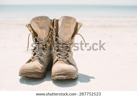 military or hiking boots in the sand. Bright sun and space to photo