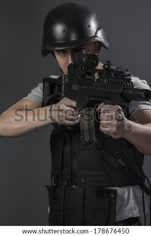 Military, paintball sport player wearing protective helmet aiming pistol ,black armor and machine gun