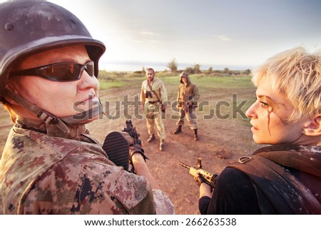 Military patrol (man and blond woman) is stopping two rebels on the road  - stock photo