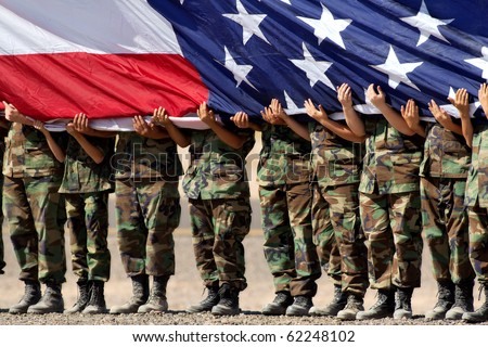 military personnel holding large American Flag - stock photo