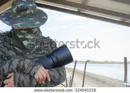 Military photographer with Big Telescope Lens and DSLR camara, while working in working field,outdoor, Technology DSLR Camare Background concept