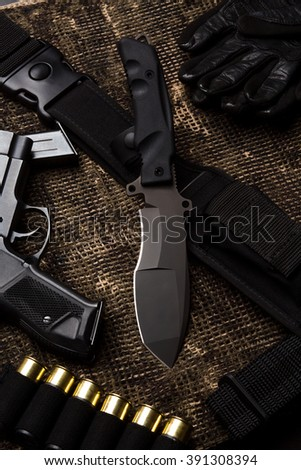 Military set: gun, gloves, rounds, knife represented on table. Army military knife with sharp edge is in centre. - stock photo