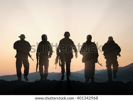 Military silhouettes of soldiers against the backdrop of sunset sky. - stock photo