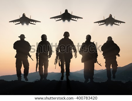 Military silhouettes of soldiers and airforce against the backdrop of sunset sky. - stock photo