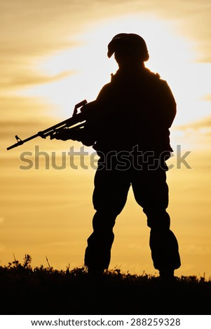 military. soldier silhouette in uniform with machine gun or assault rifle at summer evening sunset - stock photo