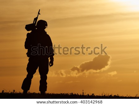 Military soldier silhouette with machine gun  - stock photo