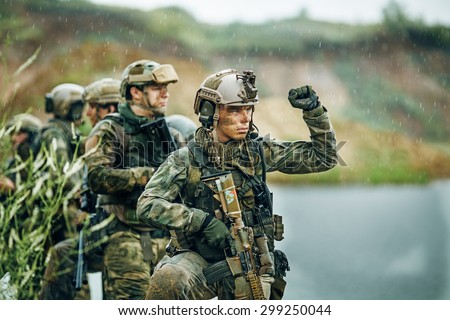 Military squad crossing the river under fire - stock photo